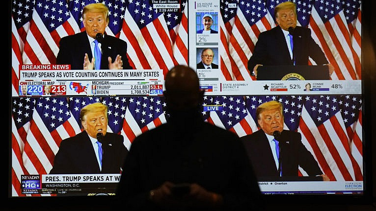 A live broadcast of Donald Trump speaking from the White House is shown on screens at an election-night party in Las Vegas. (John Locher/AP)