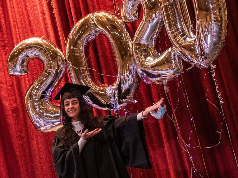 Sham Al Mukdad stands in front of balloons spelling out CTA 2020, wearing a graduation cap and gown