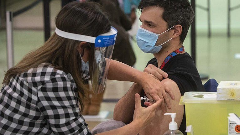 A nurse gives a COVID-19 vaccine in Edmonton, to Castro Arian in Edmonton on Tuesday, December 15, 2020. THE CANADIAN PRESS/Jason Franson