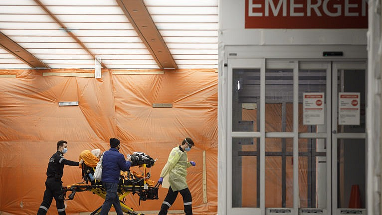 Paramedics wheel a patient into the emergency department at Mount Sinai Hospital in Toronto, on Jan. 13, 2021 (CP/Cole Burston)