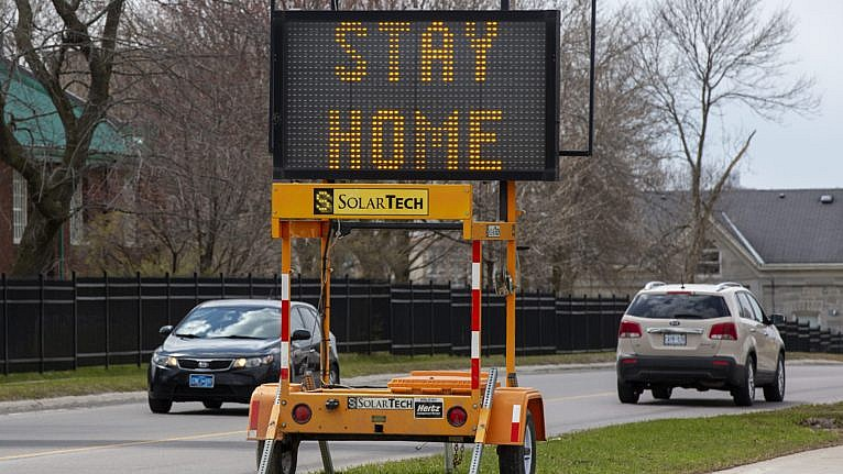 A sign tells people to stay home because of the COVID pandemic, along a road in Kingston, Ont., on April 17, 2020 (CP/Lars Hagberg)