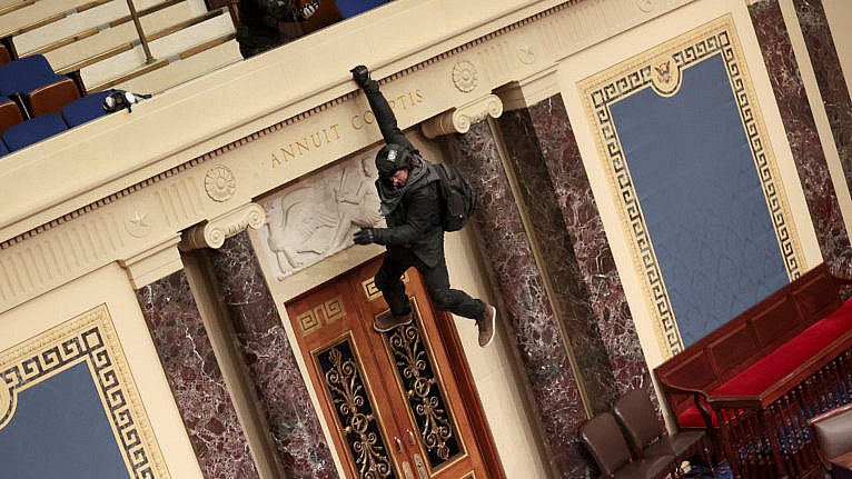 A protester hangs from the balcony in the Senate Chamber on Jan. 06, 2021 in Washington, DC (McNamee/Getty Images)