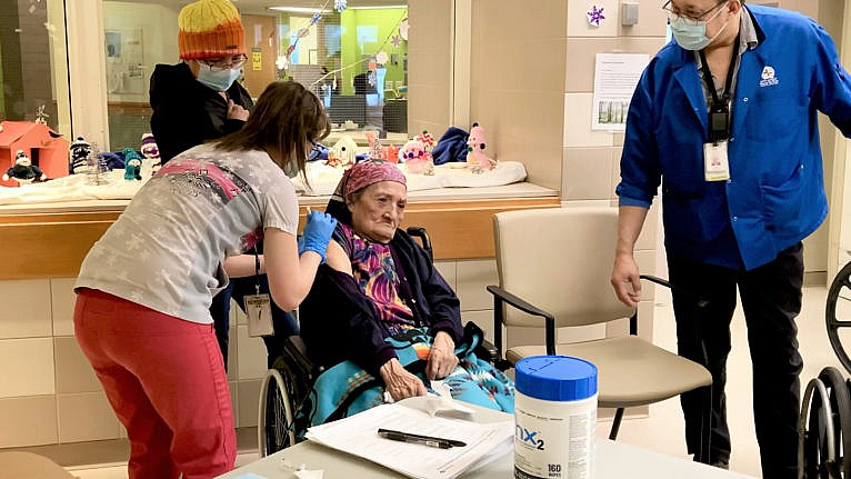 Eunice Fiddler, 85, receives a COVID-19 vaccine from Andrea McWatters as her daughter Margaret Beardy and interpreter Tom Chapman look on in Sioux Lookout, Ont. Thursday, Jan.7, 2021. THE CANADIAN PRESS/HO-Sioux Lookout Meno Ya Win Health Centre MANDATORY CREDIT