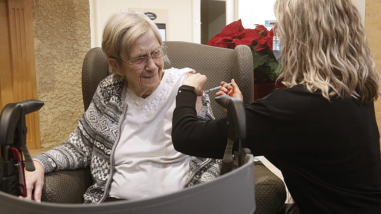 Paramedic Jessi Bittner inoculates Margaret Watson, 94, a resident at Oakview Place Long Term Care Residence, with her COVID-19 vaccine in the Winnipeg care home, Monday, January 11, 2021. Watson was the first member of the public to receive the vaccine in Winnipeg. THE CANADIAN PRESS/John Woods