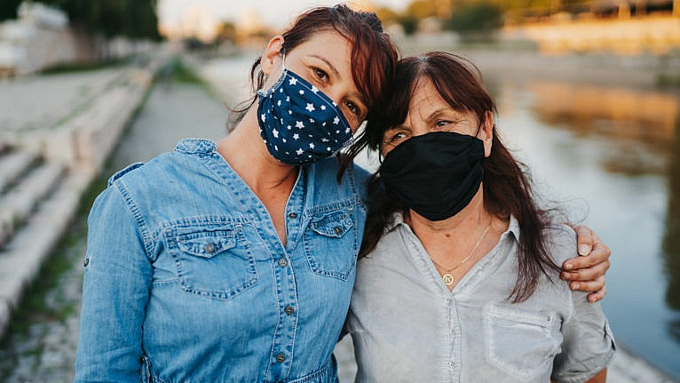 Portrait of senior woman and mid adult daughter with protective face mask standing and hugging on quayside in the city after long quarantine