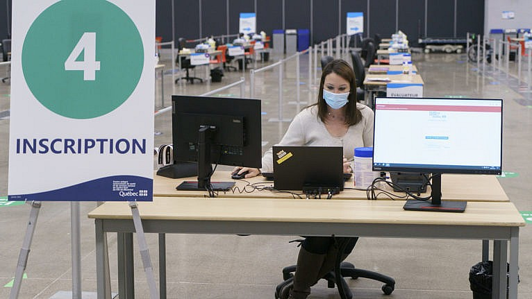A health care worker works at setting up a registration booth at a vaccination clinic in Montreal, on Monday, February 1, 2021. THE CANADIAN PRESS/Paul Chiasson