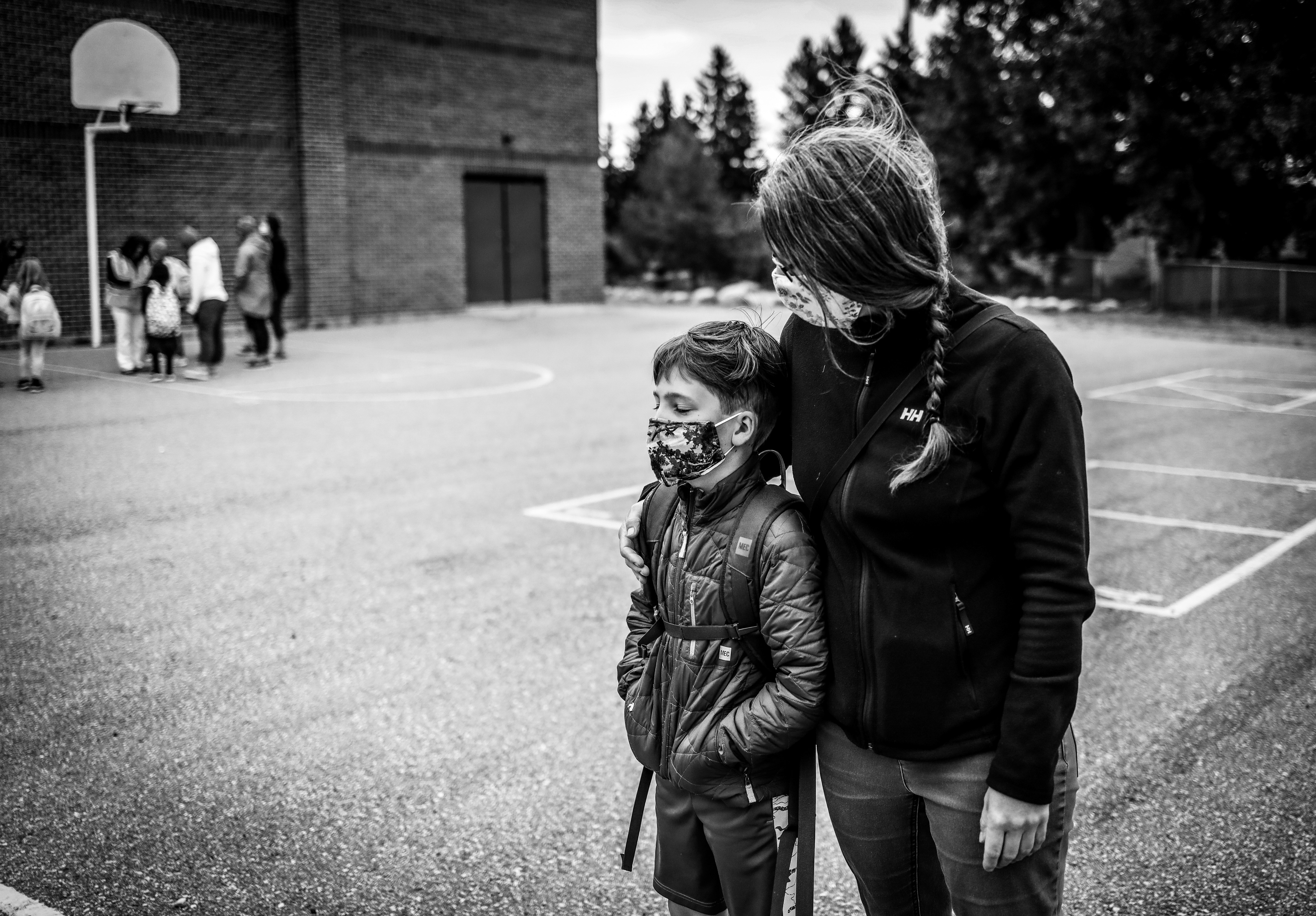 Karilynn Simpson waits in the schoolyard with her son William on his first day of Grade 4 in Calgary, on Sept. 2, 2020 (Leah Hennel)