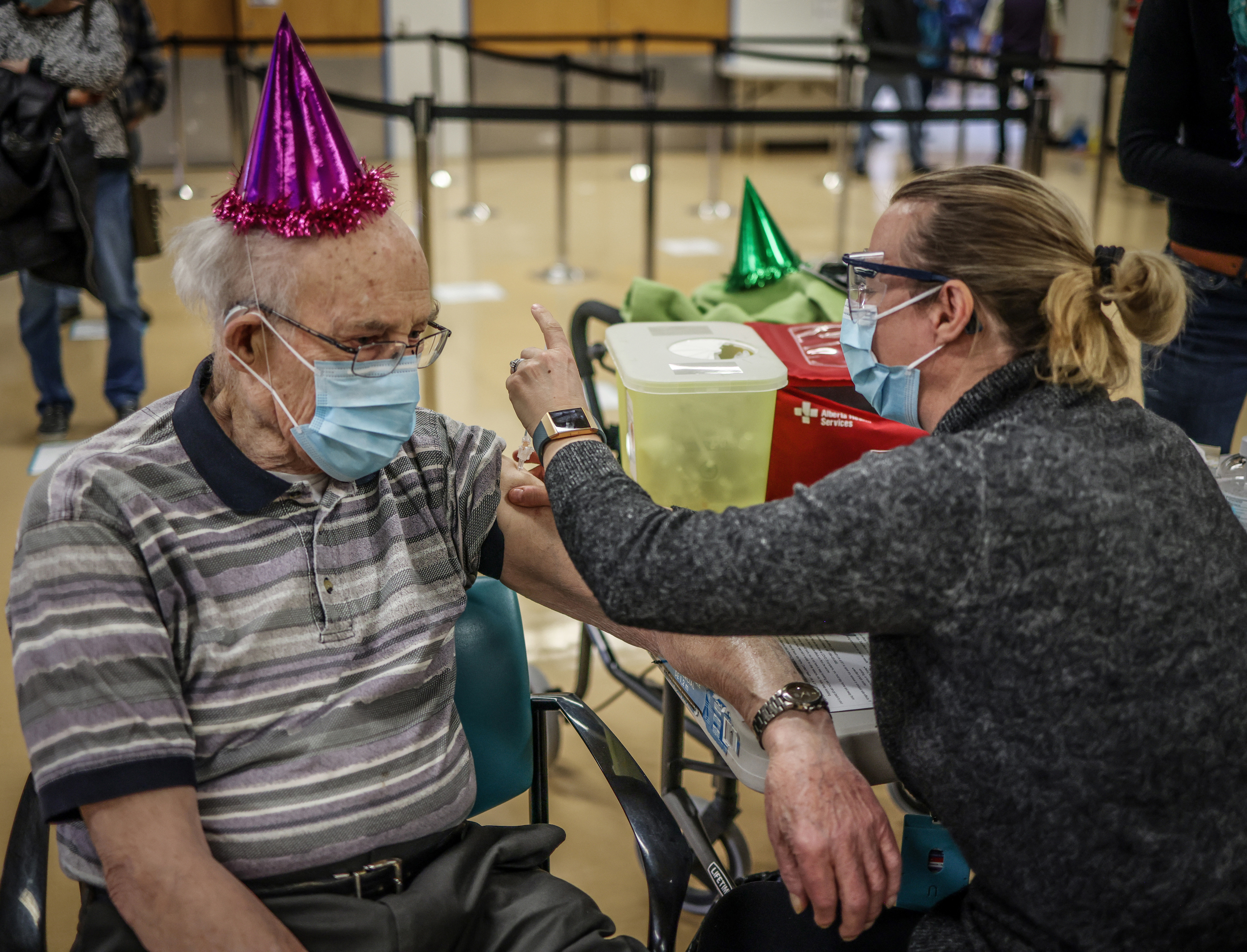 Karl Kuhnlein, 90, wears a party hat to receive his vaccination on Feb. 25 in Calgary; he's looking forward to playing pool with friends (Leah Hennel/Alberta Health Services)