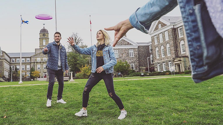 Dalhousie University students playing frisbee on campus