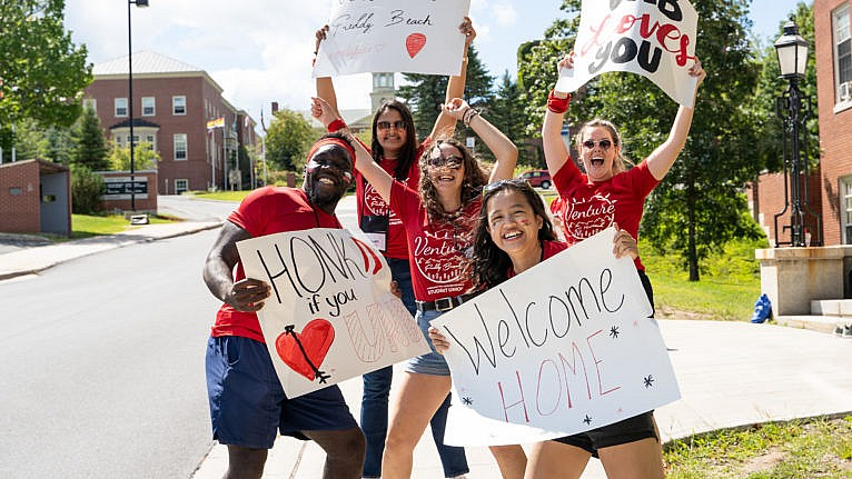 UNB students holding signs welcoming new students to campus