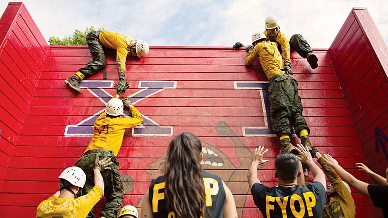 Royal Military College students scaling a wall