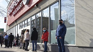 Customers wait to get into the Shoppers Drug Mart at Danforth and Coxwell as people in the age group of 60-64 line up on the other side of the store to await their Oxford-AstraZeneca COVID-19 vaccinations, in Toronto on March 11, 2021. THE CANADIAN PRESS IMAGES/Rachel Verbin