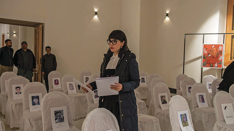 Akbar at her exhibit; each empty chair cradles the picture of a person killed by extremists (Kiana Hayeri/The New York Times)