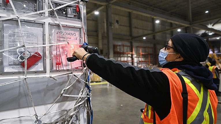 A FedEx worker scans a shipment of the Moderna COVID‑19 vaccine at Pearson International Airport in Toronto on March 24, 2021 (Nathan Denette/CP)