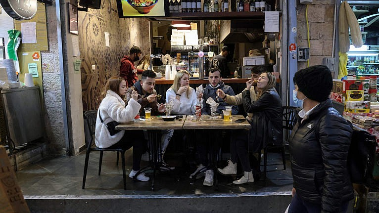 People eat at a restaurant in Jerusalem's main market after authorities reopened restaurants, bars and cafes to