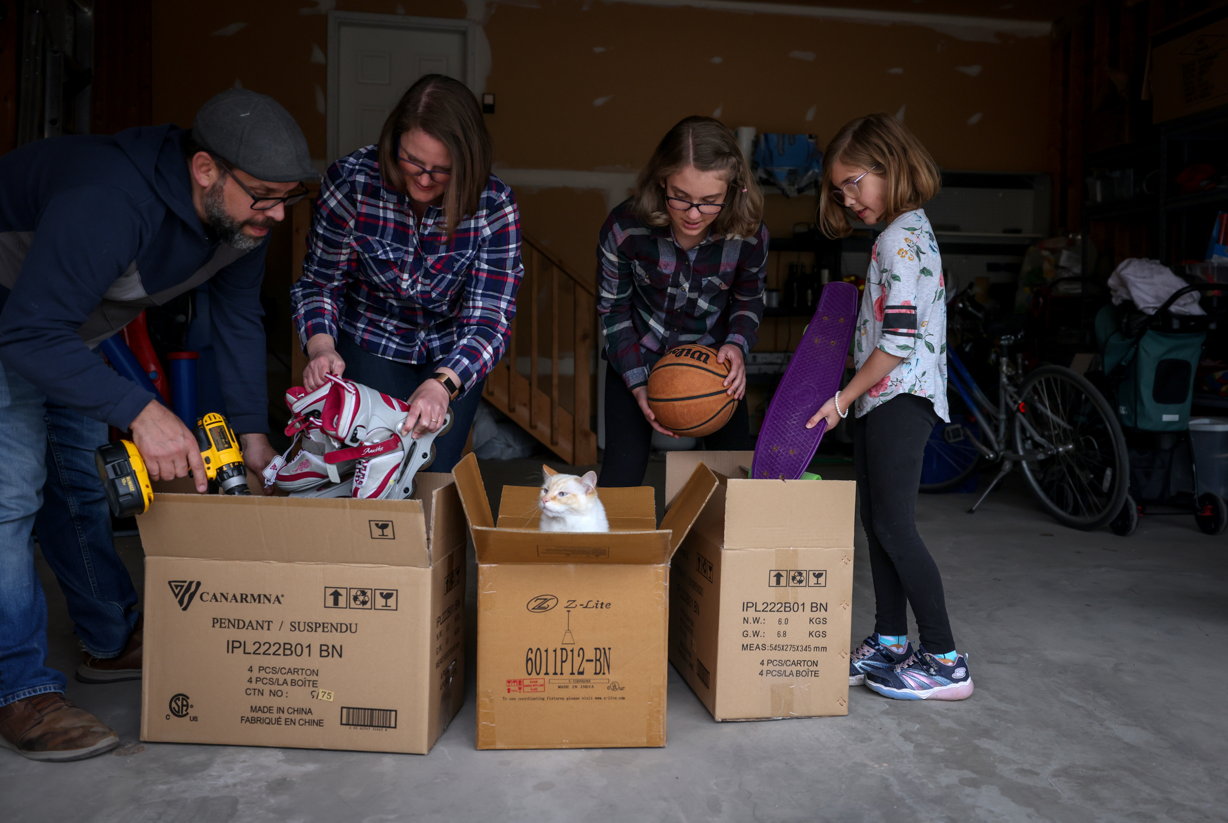 Iturriaga (left), his wife Emily, Evelyn, 12, and Bronwyn, 8, pack up their home in Calgary (Photograph by Leah Hennel)