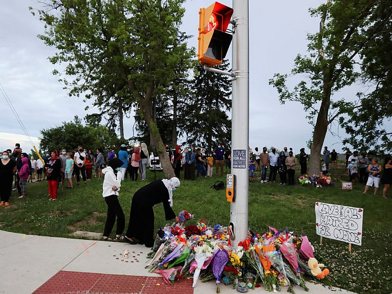 People are seen at a makeshift memorial at the fatal crime scene where a man driving a pickup truck jumped the curb and ran over a Muslim family in what police say was a deliberately targeted anti-Islamic hate crime, in London, Ontario, Canada June 7, 2021. (Carlos Osorio/Reuters)