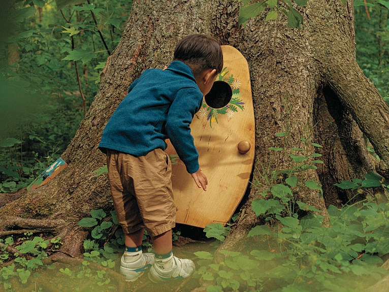 A young Guelphite stops to investigate a fairy door in Marksam Park's 'Friendly Folk Forest' (Photograph by Brendan George Ko)