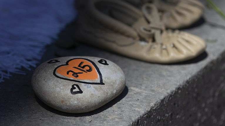 A rock with 215 painted on it is shown before a ceremony in Kingston, Ont., on Monday, May 31, 2021. The remains of 215 children were recently discovered on the grounds of the former Kamloops Indian Residential School. THE CANADIAN PRESS/Lars Hagberg