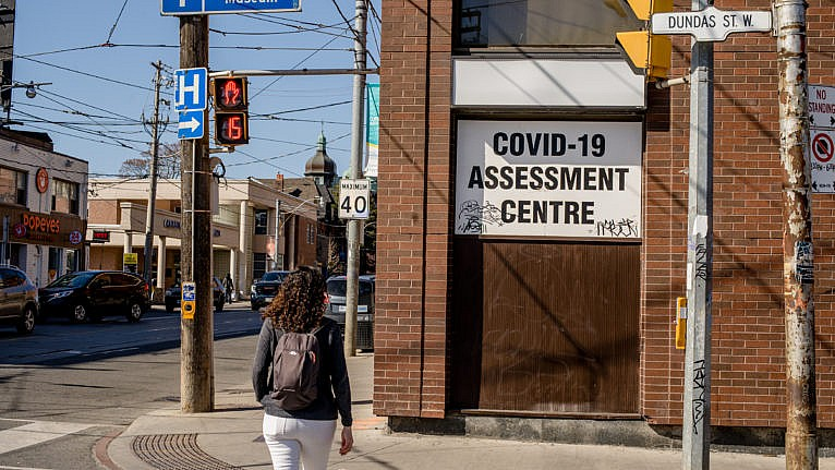 TORONTO, CANADA - 2021/03/21: Woman walks across the street, towards the COVID-19 assessment centre at Toronto Western Hospital. The COVID-19 assessment centre is where city residents go for COVID-19 testing. (Photo by Shawn Goldberg/SOPA Images/LightRocket via Getty Images)