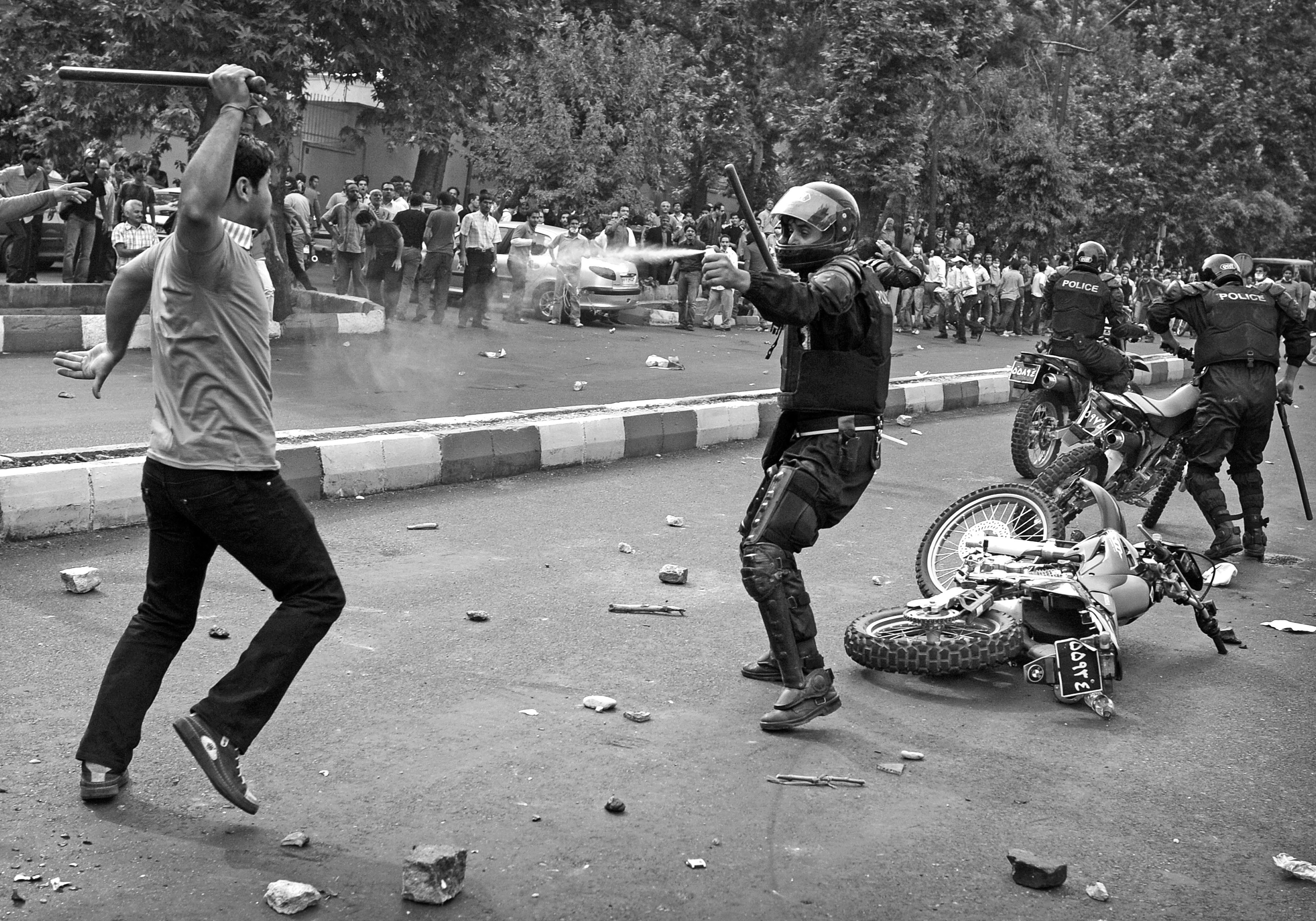 A Iranian riot-police officer sprays tear-gas at a supporter of defeated Iranian presidential candidate Mir Hossein Mousavi attacking him with a police stick during riots in Tehran on June 13, 2009. Hardline incumbent Mahmoud Ahmadinejad won a crushing victory in Iran's hotly-disputed presidential vote, according to official results that triggered mass opposition protests. (Olivier Laban-Mattei/AFP/Getty Images)