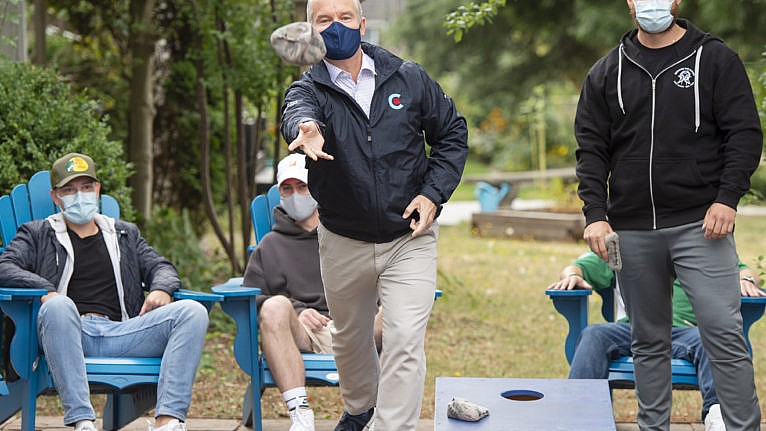 O'Toole plays a game of bean bag toss while campaigning at a drug rehab center on Aug. 22, 2021 in New Westminster, B.C. (Ryan Remiorz/CP)