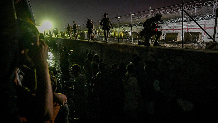 In this picture taken in the late hours on August 22, 2021 British and Canadian soldiers stand guard near a canal as Afghans wait outside the foreign military-controlled part of the airport in Kabul, hoping to flee the country following the Taliban's military takeover of Afghanistan. (Wakil Koshar/AFP/Getty Images)