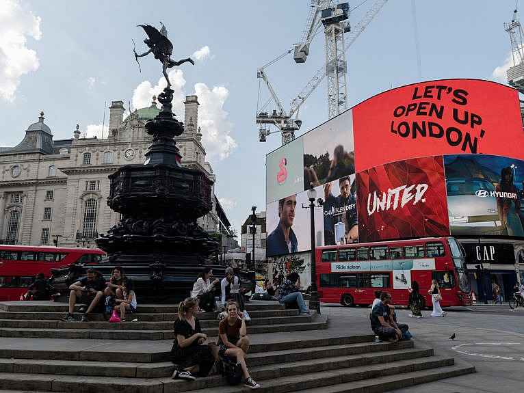 LONDON, UNITED KINGDOM - JULY 19: People sit in Piccadilly Circus as the light display reads 'Let's Open Up London' on the day of lifting of nearly all remaining coronavirus restrictions in London, United Kingdom on July 19, 2021. The removal of social and economic restrictions in England including social distancing, working from home, limits on gathering sizes and face mask mandate comes amid rapidly rising infection numbers driven by the Delta variant with UK daily Covid-19 cases exceeding 50,000 on two consecutive days last week. (Photo by Wiktor Szymanowicz/Anadolu Agency via Getty Images)