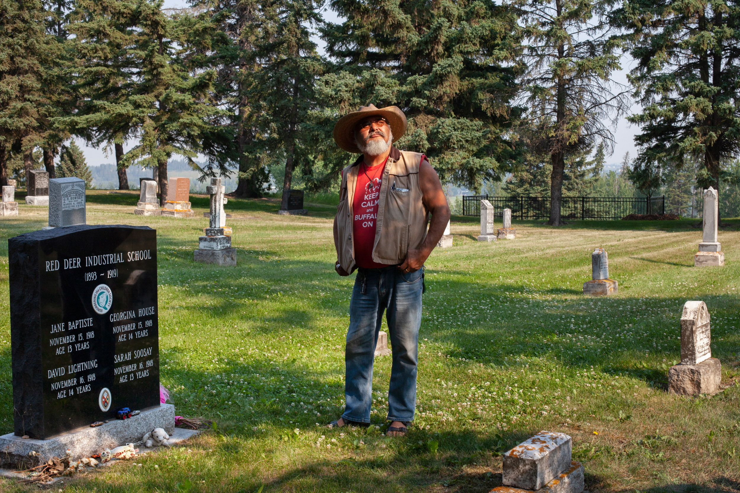Lyle Keeweatin Richards in the Red Deer Cemetery. He is standing near the grave of David Lightning. (Photograph by Jen Osborne)