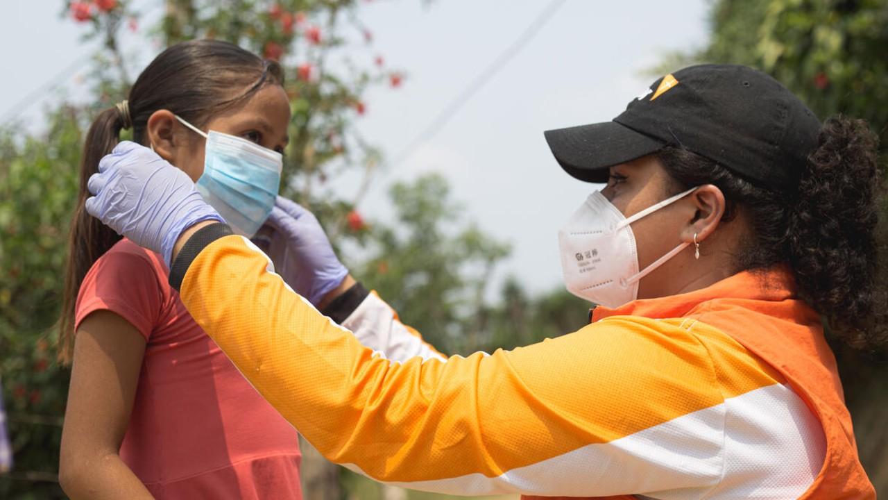 کارکنان World Vision به کودک کمک می کنند تا برای COVID-19 ماسک بزند