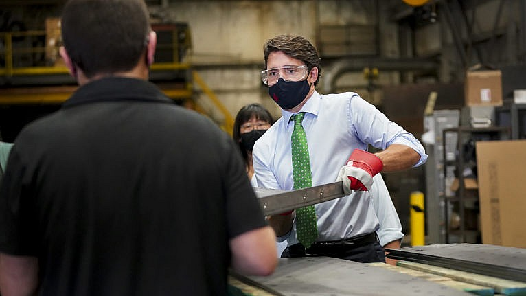 Trudeau handles a piece of steel at a campaign stop in Cambridge, Ont., on Aug. 29, 2021 (Nathan Denette/CP)