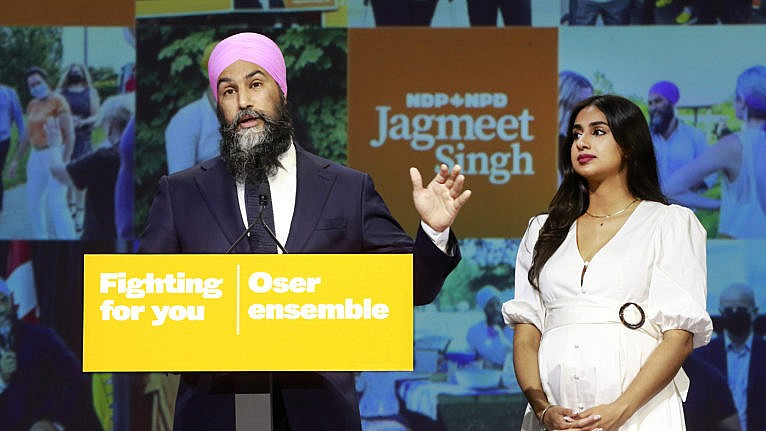 NDP Leader Jagmeet Singh stands with his wife Gurkiran Kaur Sidhu as he delivers remarks at an election night event on September 20, 2021 in Vancouver, Canada. For the first time in a decade, the New Democratic Party will have more seats in parliament than they had at the start of the election, picking up an additional three seats for a projected total of 27. (Jeff Vinnick/Getty Images)