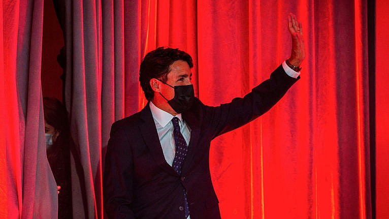 Canadian Prime Minister Justin Trudeau waves as he arrives to deliver his victory speech after snap parliamentary elections at the Queen Elizabeth Hotel in Montreal, Quebec, early on September 21, 2021. - Canadians returned Liberal Prime Minister Justin Trudeau to power on September 20 in hotly contested elections against a rookie conservative leader, according to projections by television networks. (Andrej Ivanov/AFP/Getty Images)