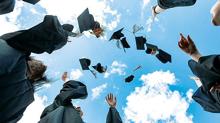 graduating students in gowns throwing caps in the air