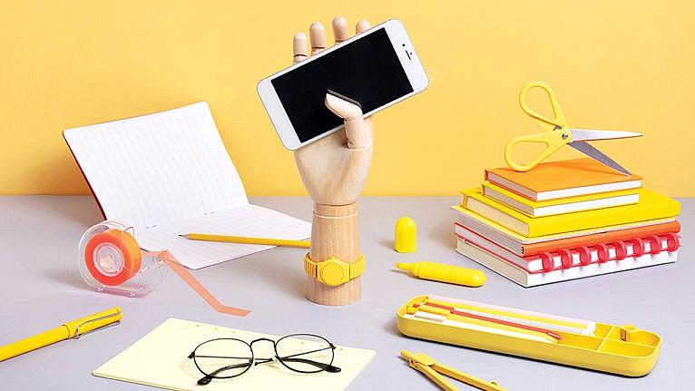 School supplies on desk with smartphone