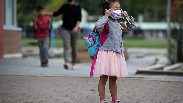 Avalynn Kwok, 4, puts on her face mask to curb the spread of COVID-19 as her parents drop her off at Lynn Valley Elementary School for her first day of kindergarten, in North Vancouver, B.C. (Darryl Dyck/CP)